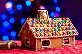 stock photo of gingerbread house  - Gingerbread house decorated with colorful candies over Christmas tree lights background - JPG