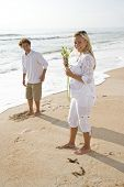 picture of sand lilies  - Young pretty pregnant woman wearing white on beach holding flower with husband - JPG