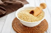 stock photo of quinoa  - Raw quinoa seeds in the bowl on wooden background closeup - JPG