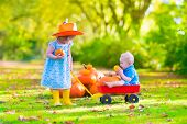 stock photo of baby cowboy  - Two happy children at pumpkin patch during Halloween cute curly little girl in a cowboy hat pushing a wheel barrow with a funny baby boy on a sunny autumn day on a farm