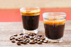 pic of mug shot  - Close up espresso shot glass and coffee bean on old wooden table - JPG