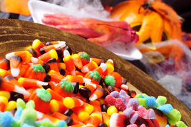 stock photo of amputation  - a pile of different Halloween candies with scary ornaments in the background - JPG