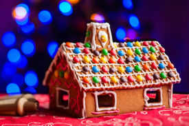 image of gingerbread house  - Gingerbread house decorated with colorful candies over Christmas tree lights background - JPG