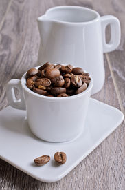 pic of milkman  - Small Cup of white filled the large coffee beans on a wooden surface - JPG