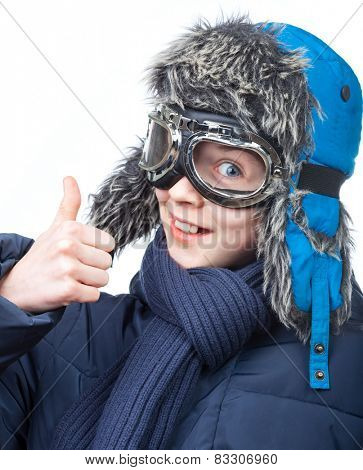 Cheerful kid wearing winter clothes showing thumb up on white background