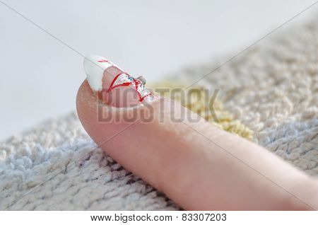 Applying nail polish on art painted manicure