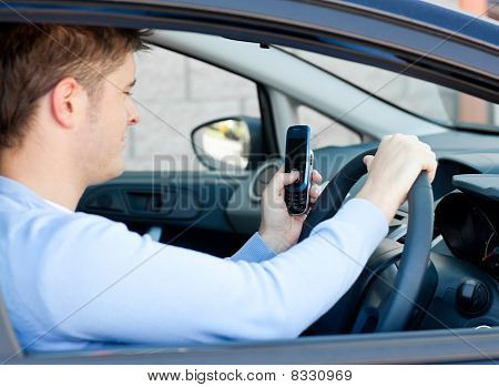 Handsome Caucasian Man Sending A Message While Driving