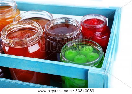 Homemade jars of fruits jam in crate on table and color wooden planks background