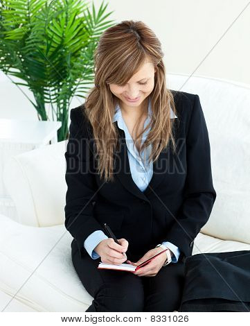 Positive Young Businesswoman Taking Notes Sitting On A Sofa