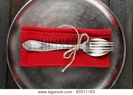 Silverware tied with rope on red napkin and metal tray on wooden background