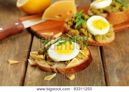 Sandwiches with green peas paste and boiled egg with cutting board on wooden planks background