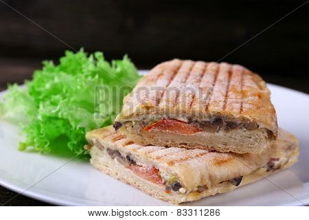 Fresh and tasty sandwiches with lettuce on plate on wooden background