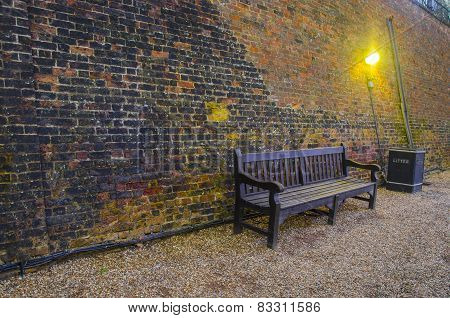 Old wooden benches in old alley with brick wall.