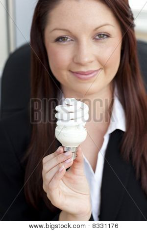 Charismatic Businesswoman Holding A Light Bulb