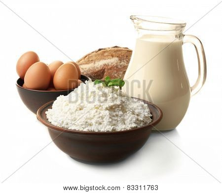 Dairy products in pottery,eggs and glass jug of milk isolated on white