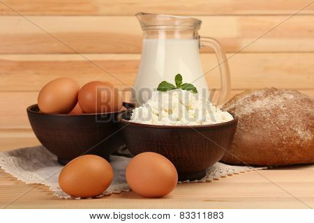 Cottage cheese in clay bowl with jug of milk, loaf of bread  and eggs on wooden planks background