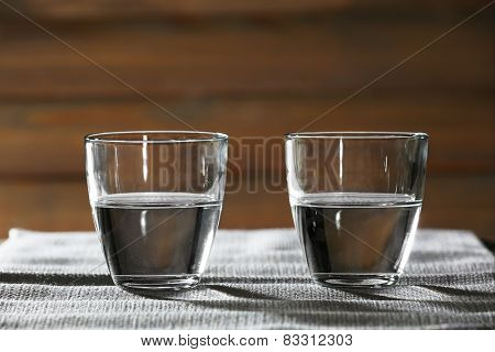 Two glasses of water on table on wooden background