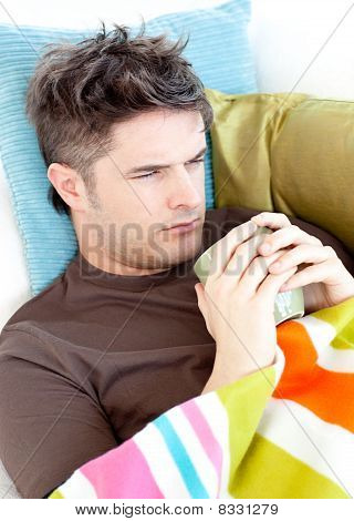 Dejected Young Man Lying On The Couch With A Hot Cup Of Tea