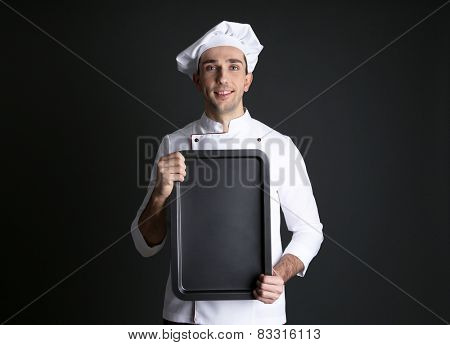 Portrait of chef with oven pan in hands on dark background