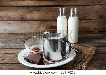 Metal mug and glass bottles of milk with chocolate chunks and strainer of cocoa on plate with burlap cloth and rustic wooden planks background
