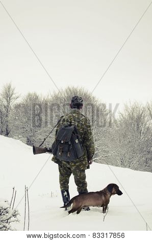 Male hunter with hunt dog on snowy weather