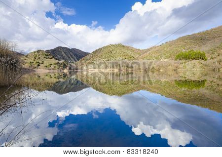 Sky clouds and hils reflection on lake