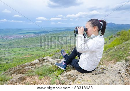 Girl with binoculars on a peak enjoying the view