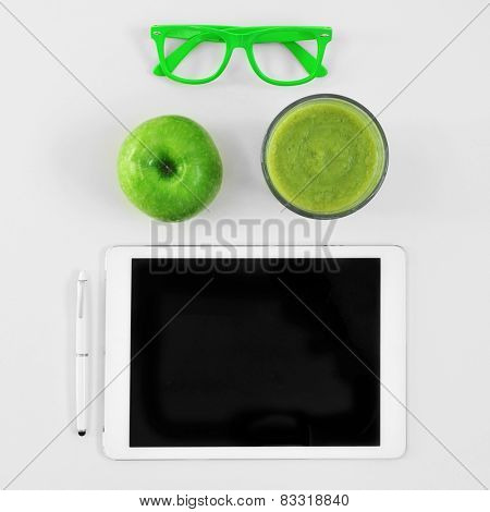 high-angle shot of a table with a pair of green plastic-rimmed eyeglasses, an apple, a glass with a green smoothie and a tablet computer