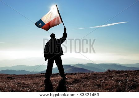 Man on a mountain top holding the flag of Chile