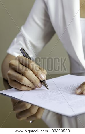 a woman signing a contract