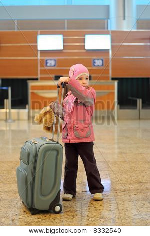 Little Girl With Grey Suitcase Standing Alone At Airport