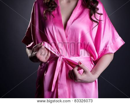 Girl tying belt of her silk robe, close-up