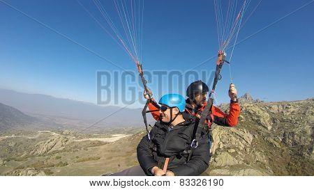 Two men paragliding high above mountain range