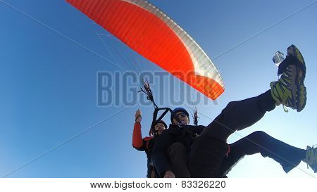 Two men with orange paraglider against blue sky
