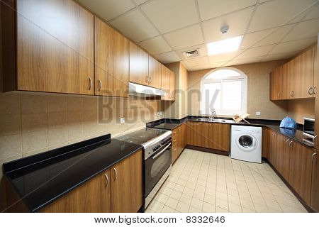 Kitchen With Brown Cupboards, Washingmachine And Cooker