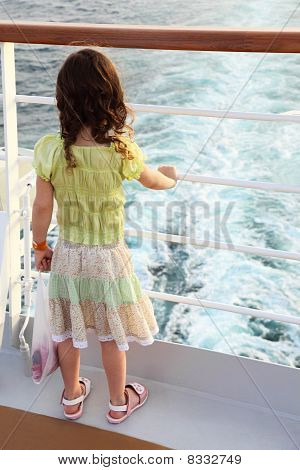 Little Curl Girl Standing On Ship Deck And Looking On Waves