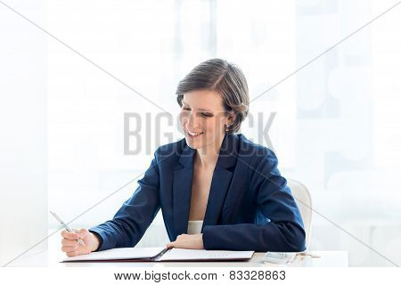 Happy Businesswoman Writing Financial Report At Her Table