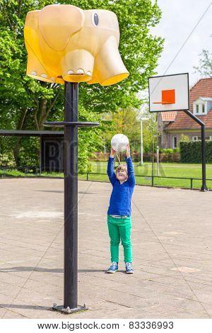 Young girl aiming ball at basket like elephant