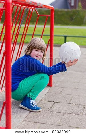 Young girl with ball in red metal goal