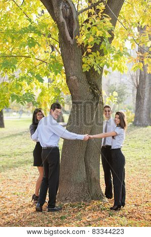 Young Business People Hugging Tree
