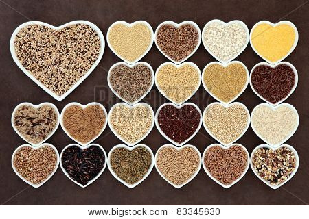 Grain and cereal food selection in heart shaped porcelain bowls over lokta paper background. Tricolour quinoa in large dish.