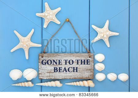 Gone to the beach sign with starfish, cockle and turritella seashells over wooden blue background.