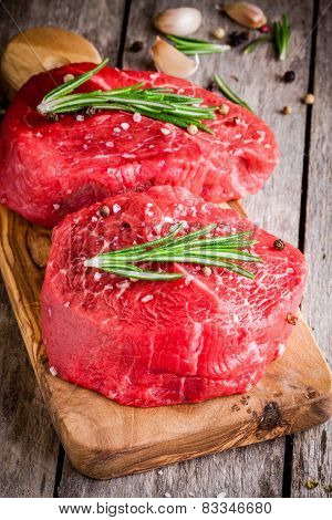 Two Raw Steaks With Rosemary, Garlic, Salt And Pepper