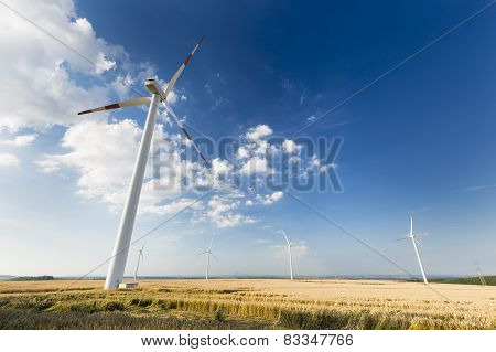 Tall Wind Turbine Overlooking Smaller Wind Turbines