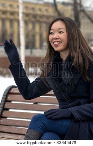 happy Asian woman a friendly wave of his hand