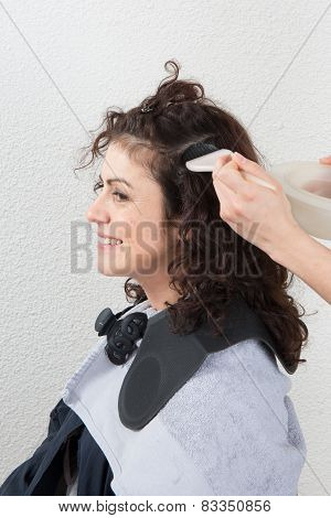Woman Having Her Hair Dyed By Beautician At Parlor