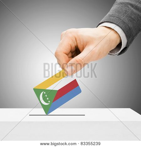 Voting Concept - Male Inserting Flag Into Ballot Box - Comoros