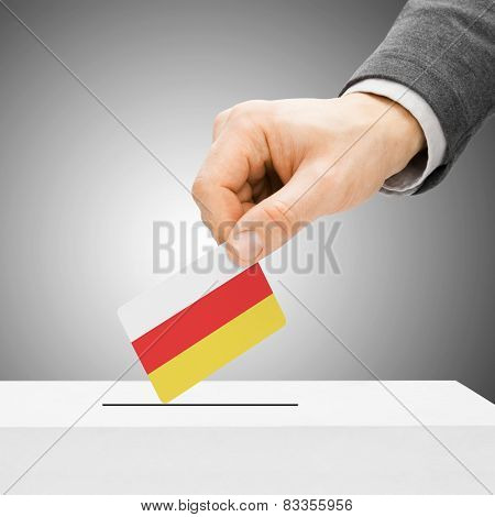 Voting Concept - Male Inserting Flag Into Ballot Box - South Ossetia
