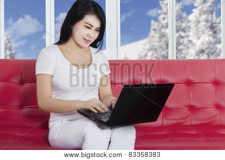 Casual Woman Using Laptop On Couch