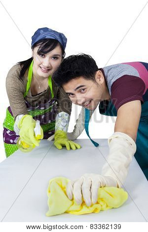 Joyful Couple Cleaning A Table